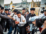 22 MAY 2015 - BANGKOK, THAILAND: Anti-coup protestors scuffle with police during a protest in front of the Bangkok Art and Culture Centre Friday evening. The Thai military seized power in a coup on May 22, 2014. There were small protests throughout Bangkok Friday to mark the first anniversary of the coup. Police arrested protestors at several locations. The most serious protest was at Bangkok Art and Culture Centre (BACC) where about 100 protestors, mostly students, faced off against police for several hours. Police made numerous arrests at the BACC protest.     PHOTO BY JACK KURTZ