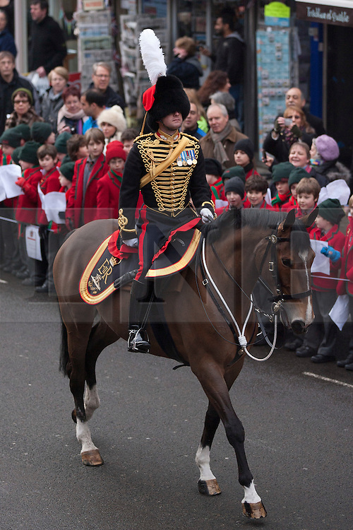 © Licensed to London News Pictures. 06/02/2012. LONDON, UK. A officer of the Kings Troop Royal Horse Artillery rides past school children and members of the public as his unit parades on St John's Wood High Street during a farewell ceremony there. Gunners of the Kings Troop, based at St John's Wood since 1947, today (06/02/12) left their barracks for the last time to fire their guns in Hyde Park, the soldiers will move tomorrow to their new home in Woolwich. Photo credit: Matt Cetti-Roberts/LNP