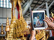 """19 DECEMBER 2016 - BANGKOK, THAILAND: A person photographs a Thai Royal Chariot at the Bangkok National Museum. A """"Spirit Appeasing"""" Ceremony was held for the Royal Chariots at the Bangkok National Museum. The chariots will be used to take the body of Bhumibol Adulyadej, the Late King of Thailand, and members of the Royal funeral cortege to the cremation site on Sanam Luang for His Majesty's cremation. This will be the first cremation of a Thai King since 1950, when King Bumibol's brother, Rama VIII, Ananda Mahidol, was cremated. The design of the royal crematorium is based on Buddhist cosmology, with the main peak of Mount Sumeru (also known as Meru in Hindu cosmology) at center and eight other peaks signifying the levels of the universe. The crematorium will be decorated with mythical creatures such as garuda, angels, and Himmapan Forest creatures. The structure and funeral pyre will stand just over 50 meters tall. The exact date of the King's cremation has not been set yet but is expected to be late next year.     PHOTO BY JACK KURTZ"""