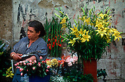 A middle-aged woman florist sells flowers at her stall in Alfama, on 21st March 1994, in Lisbon, Portugal.