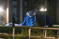 © Licensed to London News Pictures. 31/05/2021. London, UK. A police officer stands next to a forensic tent at the crime scene at Montrose Park, Edgware following the fatal stabbing of an 18-year-old male. Metropolitan Police were called at 17:54 BST on Monday 31/05/2021 following reports of a group of males fighting. The man was found suffering from a stab injury in a tennis court area. He was treated by London's Air Ambulance and London Ambulance Service at the scene but was pronounced dead at 19:19 BST. Photo credit: Peter Manning/LNP