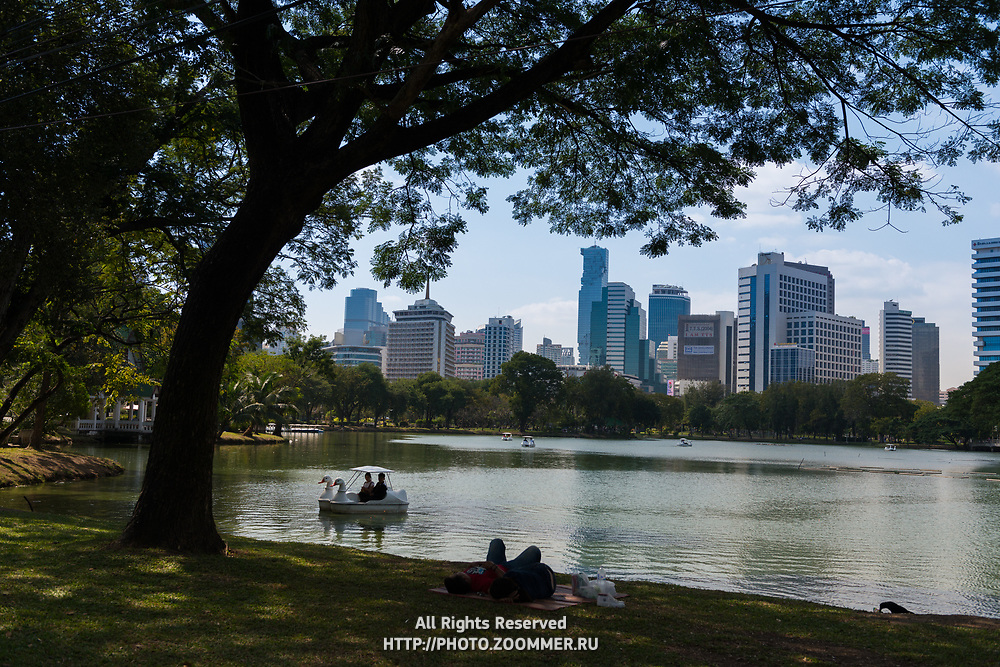 People relax on grass near lake in Lumpini park, Bangkok, Thailand