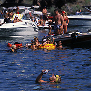 """Scott Chamber, in water drinking beer, parties on Lake Havasu during Memorial Day weekend. Each year there are several incidents of """"prop chop"""" where people in the water are injured by boat props."""