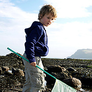 A young boy with a fishing net in his hand, Robin Hood's Bay, North Yorkshire, UK