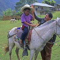Senor Richard Rey Cotrima, el presidente de la fiesta in Yamblon, Peru, taks with his son who is sitting on a horse.