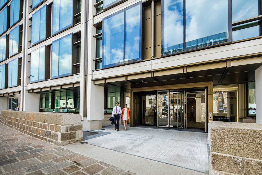 Businesman and woman leaving the corporate offices of the International Finance Centre in St Helier, Jersey