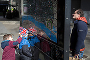 Tourists study a map of the City of London, the capital's financial district, on 25th March 2019, in London, England.