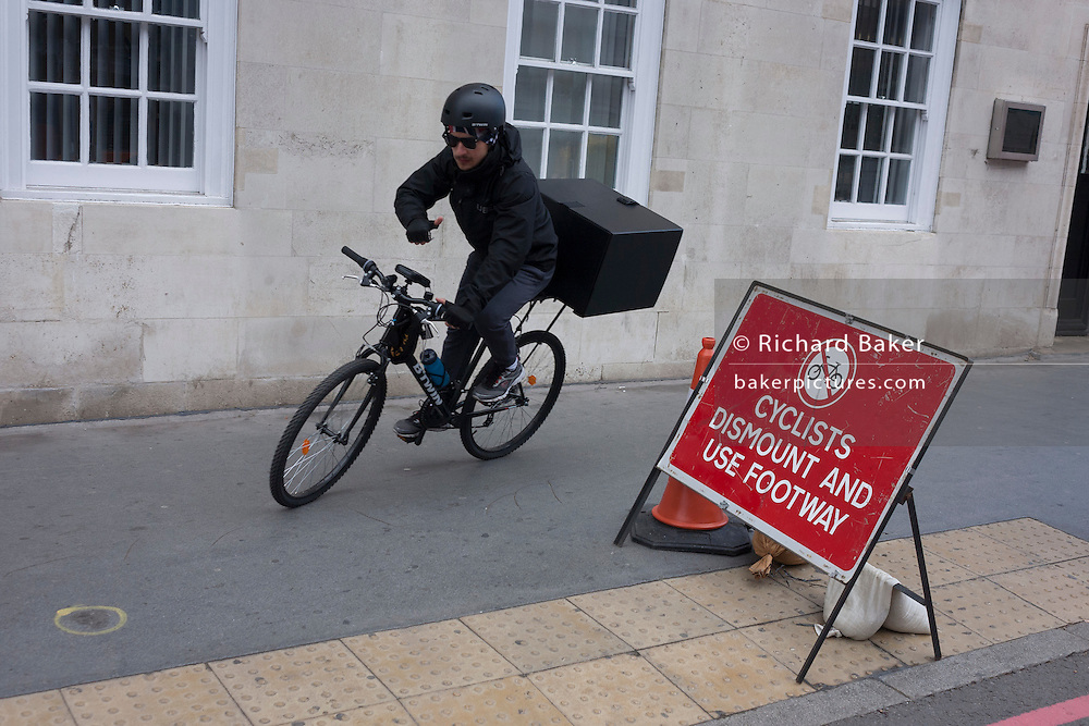 A delivery courier ignores a cyclist's dismount sign on the southern side of London's Tower Bridge, closed for repairs to traffic and disrupting this major Thames crossing and surrounding roads for the next three months.