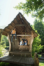 Two boys and a girl on a cottage in the adventure playground, Munich, Bavaria, Germany