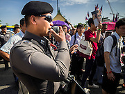 07 JULY 2015 - BANGKOK, THAILAND:   A Thai police officer makes announcements to people gathered at the Ministry of Defense in defiance of military orders against political rallies. At least two people were arrested during the rally. About 100 people gathered in front of the Ministry of Defense in Bangkok Tuesday to support 14 university students arrested two weeks ago for violating orders against political assembly. They're facing criminal trial in military courts. The courts ordered their release Tuesday because they can only be held for two weeks without trial, the two weeks expired Tuesday and the military court chose not to renew their pretrial detention. The court order was not an acquittal. They still face trial and possible prison sentences if convicted.      PHOTO BY JACK KURTZ