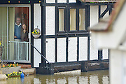 © Licensed to London News Pictures. 09/01/2014. Marlow, UK. A couple look at out at the flood water approaching their property. Rising river levels in the River Thames at Marlow in Buckinghamshire have led to flooding and property damage along the river today 9th January 2014. Large areas of Britain are experiencing flooding after wet weather. Photo credit : Stephen Simpson/LNP