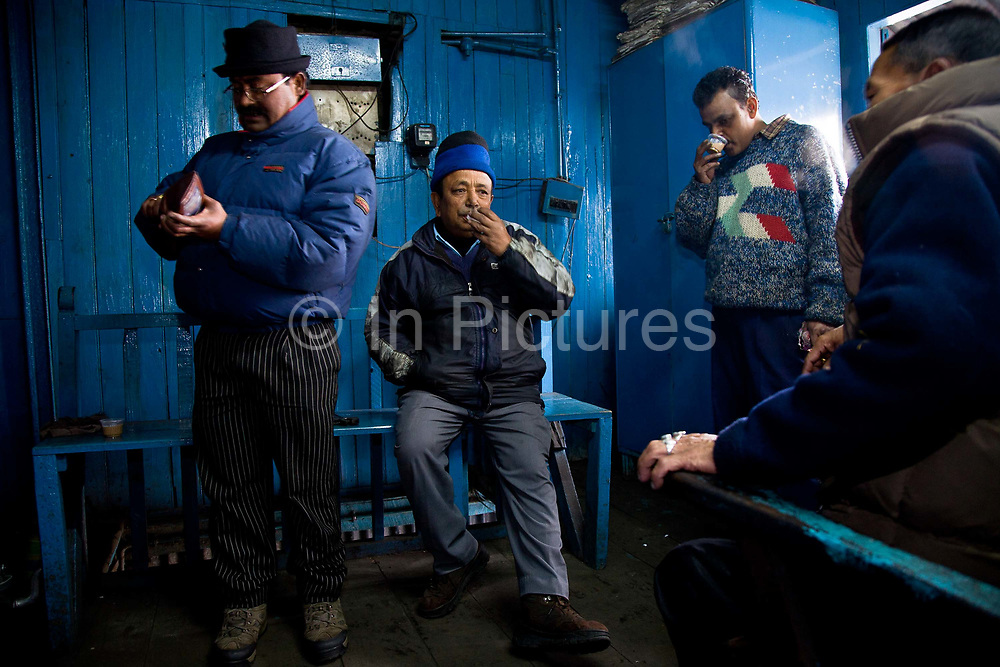 """Train drivers and maintenance staff assemble at Darjeeling railway station to begin the day's journeys and maintenance planning.  The Darjeeling Himalayan Railway, nicknamed the """"Toy Train"""", is a narrow-gauge railway from Siliguri to Darjeeling in West Bengal, run by the Indian Railways. It was built between 1879 and 1881 and is about 86 km long. The elevation level is from about 100 m at Siliguri to about 2200 m at Darjeeling. It is still powered by a steam engine and travels daily between the two towns, as well as a shorter route to Kurseong.  It is now classed as a World Heritage Site by UNESCO. India."""