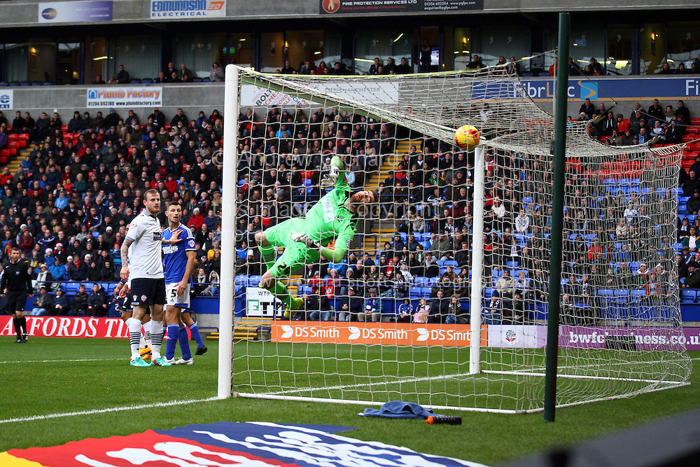 Bolton Wanderers Goalkeeper Andy Lonergan tips the ball over the bar as he saves from Daryl Murphy of Ipswich (not in pic). . Skybet football league championship match, Bolton Wanderers v Ipswich Town at the Macron stadium in Bolton, Lancs on Saturday 13th December 2014.<br /> pic by Chris Stading, Andrew Orchard sports photography.