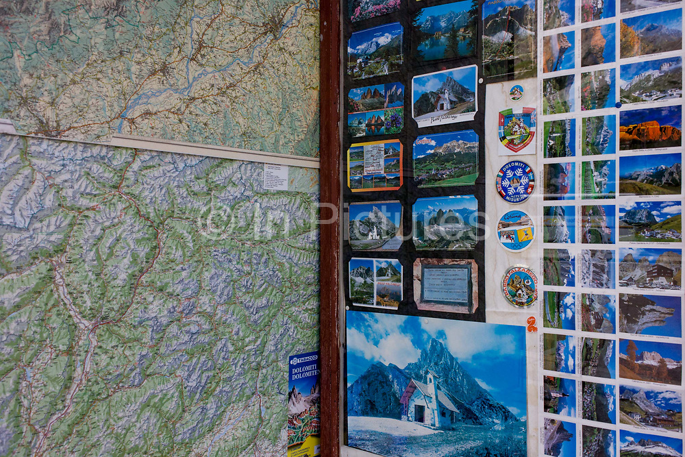 Detail of postcard souvenirs of a map and Dolomite mountain scenes in a shop selling tourist memorablia on Passo Falzarega (Pass) in south Tyrol, Italy. With just half a million inhabitants, south Tyrol attracts nearly 6m holidaymakers annually who total 29m overnight stays a year. The Dolomites are a mountain range in northeastern Italy and in August 2009, the Dolomites were declared a UNESCO World Heritage Site.