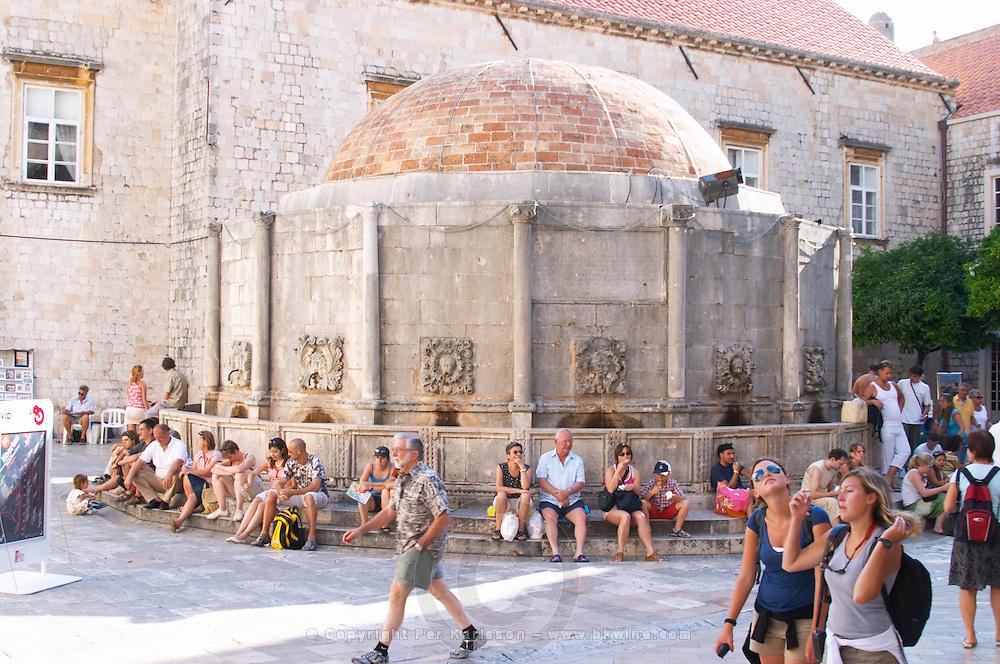 Tourists sitting around the Grand Big Onofrio fountain velika Onofrijeva Placa Stradun Dubrovnik, old city. Dalmatian Coast, Croatia, Europe.