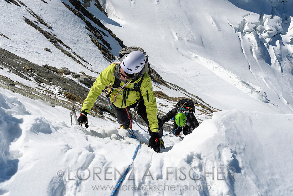 Two alpinists are climbing up the south face of the Dent d'Herens, Aosta Valley, Italy