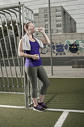 Young woman drinking water on football ground, Bavaria, Germany
