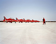 Single pilot of the Red Arrows, Britain's RAF aerobatic team walks out to his Hawk aircraft before a display flight to Jordan. In the mid-day heat, Flt. Lt. Jez Griggs is a member of the elite 'Red Arrows', Britain's prestigious Royal Air Force aerobatic team. Here he walks out alone to his aircraft, which is lined up with some of the others jets at RAF Akrotiri, Cyprus before flying out to Marka in Jordan for the first display of the year. The Red Arrows arrive each April to fine-tune their air show skills in the clear Mediterranean skies and continue their busy display calendar above the skies of the UK and other European show circuit. We see Griggs carrying his flight bag and life-vest. He paces confidently across the bright 'apron' dressed in his famous red flying suit that the Red Arrows have made famous since 1965. He is alone and striding confidently towards the matching red eight Hawk airplanes.