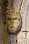 Ancient cared stone face in exterior wall, Holy Trinity Church, Long Melford, Suffolk, England, UK