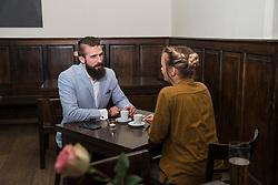 Young couple talking at restaurant while sitting by dining table with coffee cup