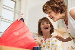 Senior woman showing shopping bag to her friend in the kitchen, Munich, Bavaria, Germany