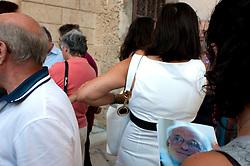 Alessano 23 luglio 2010.Marcello Torsello, inaugurazione mostra Ritagli di Cielo.. <br /> Le vicende della pittura di Marcello Torsello, seppure innestate da poco nel panorama dell'arte italiana, lasciano leggere dichiarazioni di attualità, dove passato presente e futuro si svelano.annodati al filo del desiderio. Ed è proprio questo filo del desiderio a riannodare il discorso dell'opera - ove transita.il capitolo del presente e la recherce du temp perdu - al soggetto, alle motivazioni profonde, alla struttura fantasmatica che dentro gorgoglia e fa affiorare in superficie un brano di storia, di storia contadina, di architettura del sud, di spaccato del territorio che l'artista conosce... Molti vorrebbero in questo caso stucchevolmente parlare.di pittura di paesaggio, niente di tutto ciò, perchè il paesaggio di Marcello Torsello se da una parte guarda.all'americano Edward Hopper per una sorta di pittura silenziosa, calma, stoica, luminosa e classica, dall'altra si.allontana dalle forme e dall'iconicità, per segnalarsi come addirittura svolta astratto-geometrica, per via dei tagli e.delle scenografie, per via dei ritagli di cielo, per via di certi comignoli sui tetti che sono fortemente evocativi,.immagini avvolte nella luce e nell'ombra, addirittura fantasmi dei luoghi. Case, tetti, facciate, comignoli, finestre, porte, diventano spazi senza confini, in un tempo dilatato, in un tempo che accoglieva la vita e oggi lascia sfumare.l'oscurità dei ricordi. Questo paesaggio improprio diventa lo spazio e il tempo dell'esperienza onirica, della.ricchezza irriducibile dei sogni. Marcello Torsello dipinge la realtà distaccandosi da essa, ma senza perdere il.legame con essa. Usa la materia e il colore per raggiungere la dimensione spirituale dei ricordi,la malinconia del.silenzio. Il silenzio degli spazi della memoria. Nel segno della reverie, la consistenza degli elementi, specie i comignoli, sono i gradi della realtà, e sono proprio questi gradi a far leggere ...