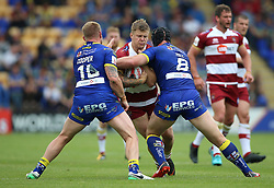 Warrington Wolves Mike Cooper (left) and Chris Hill (right) tackle Wigan Warriors Ryan Sutton during the Ladbrokes Challenge Cup, quarter final match at the Halliwell Jones Stadium, Warrington.