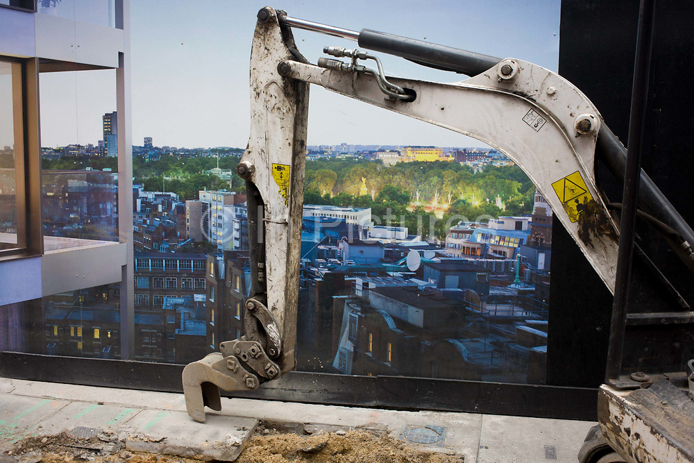Digger arm and construction hoarding illustration. The background of a utopian view from this new development in London's Victoria district is juxtaposed with the dirty reality of the construction equipment that rests, its arm on the pavement having just broken up old paving stones.