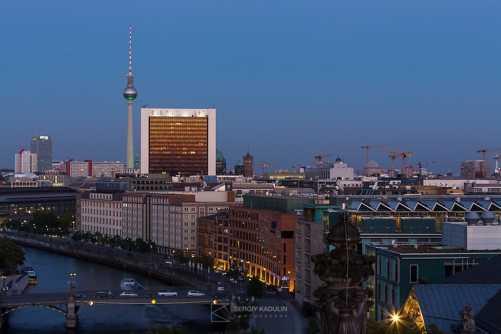 Berlin's cityscape, bird's eye view from the roof of Reuchstag building. Includes buildings of government district, Shpree river with bridges and TV Tower in the background. Evening view near sunset.