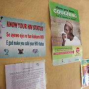 INDIVIDUAL(S) PHOTOGRAPHED: N/A. LOCATION: Ikeja Primary Health Care Center, Lagos, Nigeria. CAPTION: Informational posters about tuberculosis and HIV/AIDS are displayed in the main waiting room at the Ikeja Health Center.