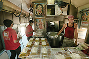 Kitchen staff. Open windows provide little relief from India's scorching May heat in the kitchen compartment. Thali, platters of rice, daal, and curry, are served aboard the train and delivered directly to passengers' compartments. Unfortunately, most of the plastic trays are thrown out the window. Inside the Dibrugarh-Kanyakumari Vivek Express, the longest train route in the Indian Subcontinent. It joins Kanyakumari, Tamil Nadu, which is the southernmost tip of mainland India to Dibrugarh in Assam province, near the border with Burma.