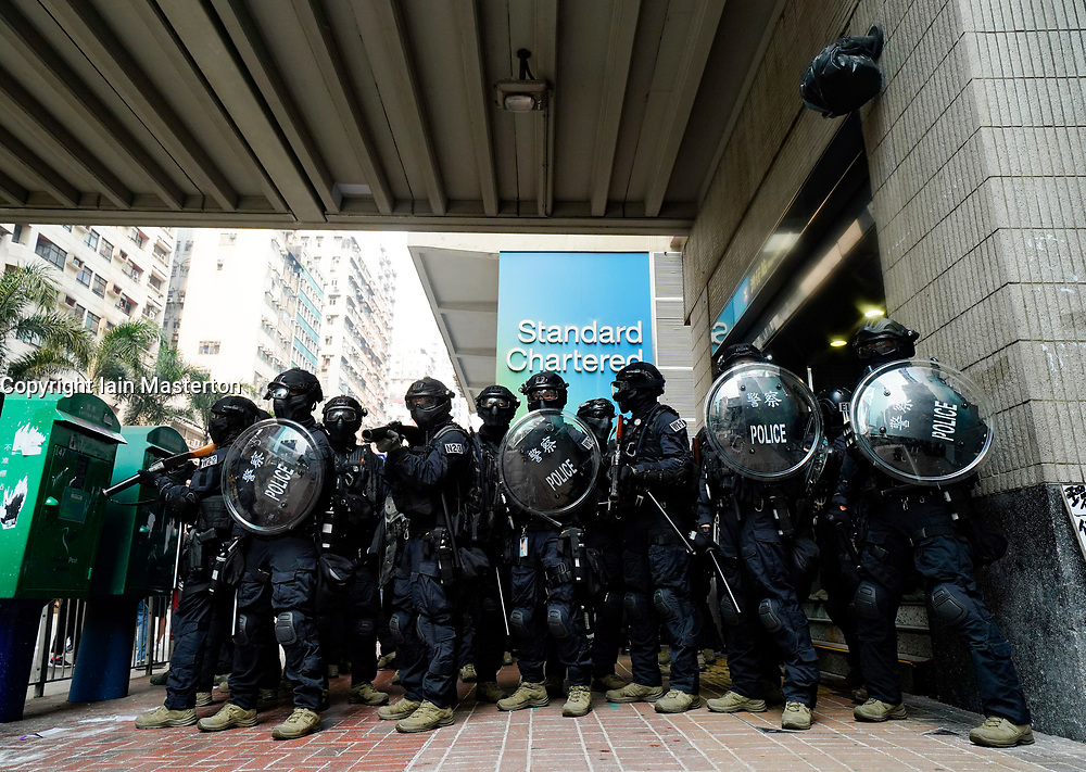 Hong Kong. 29 September, 2019. Illegal march by thousands of pro-democracy supporters from Causeway Bay to Government offices at Admiralty. Police unsuccessfully tried to stop march at start with teargas fired and scuffles. March marked the 5th anniversary of the start of the Umbrella Movement. Riot police guard entrance to Wanchai MTR station
