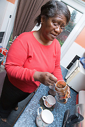 Older woman in her kitchen spooning coffee into a cup,