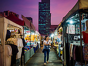 05 MARCH 2019 - BANGKOK, THAILAND:  A woman walks down an aisle in the Ratchada Night Market. The AIA Capital Center Building is in the background. The Ratchada Night Market is the newest night market in Bangkok. It was originally a small night market popular with local people but now is tourism destination. Most nights the market is jammed with foreign tourists.   PHOTO BY JACK KURTZ