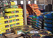 Fertiliser bags and other garden products piled on pallets in Notcutts garden centre