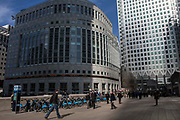 City workers cross the plaza outside the Thompson Reuters building at 30 South Colonnade, Canary Wharf, Docklands, London, United Kingdom. There is a line of Barclay's Boris bikes which Londoners use to travel across the city. The sun lights up One Canada Square, probably the most iconic skyscraper in London.