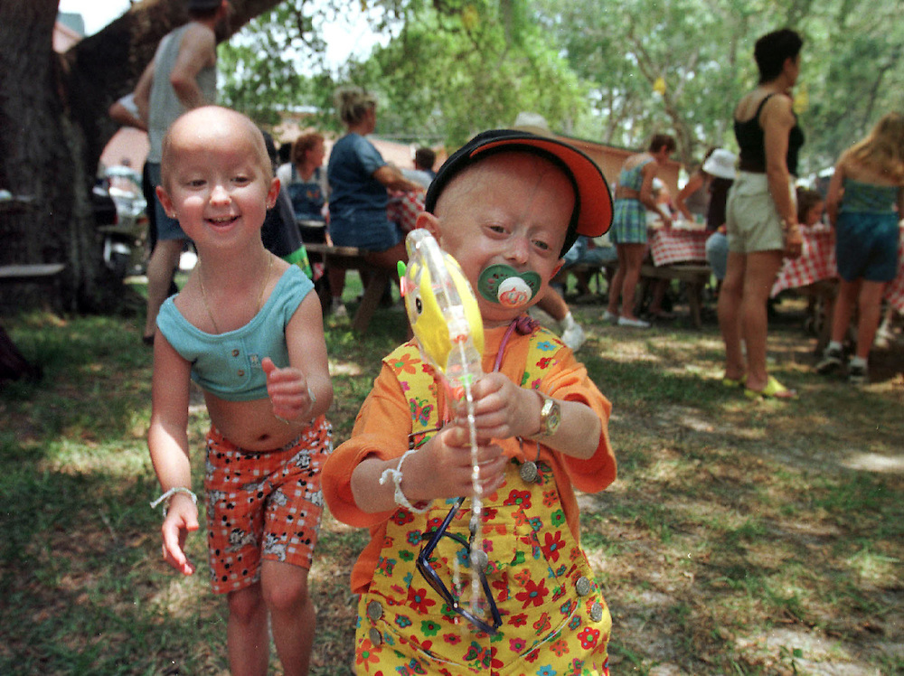 POLK RIVER RANCH 6/20/98-POKIDS- Sarah Rodler,4,of Austria takes her turn soaking bystanders as her friend Megan Durel,5, of France looks on Saturday. The girls frolicked in the afternoon sun during a picnic that kicked off the Sunshine Foundation's week long gathering for children diagnosed with the rare disease progeria.(staff/scott iskowitz)