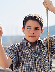 boy in plaid shirt holding a rope outdoors