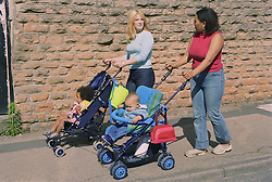 Young mothers pushing children in pushchairs along pavement,