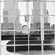 view through window of a picture of an american flag on a building roof with skyscrapers in the background