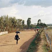 Man walking down a street under a sun shade umbrella in Lalibela, Ethiopia
