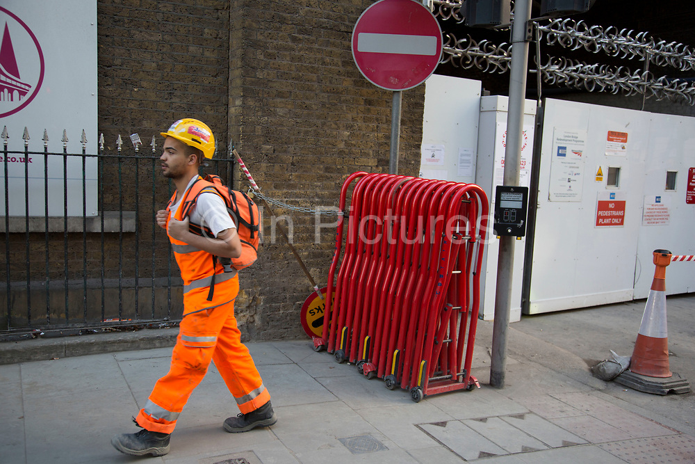 Workmen wearing high viz safety clothing at the construction site on Tooley Street for London Bridge station redevelopment. UK.