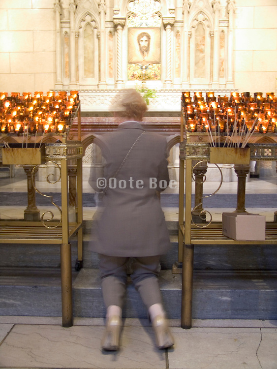 woman praying in front of votive altar with cloth of Jesus portrait.