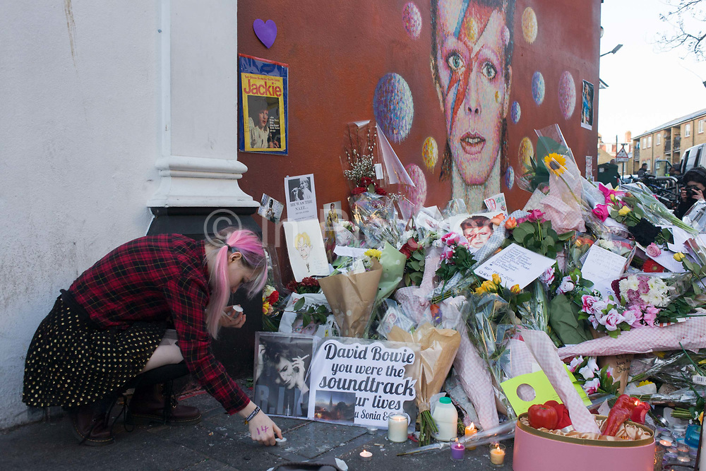 London 12th January 2016: Fans of iconic English music artist David Bowie who died from Cancer at the age of 69 on Sunday 10th January, gather to pay their respects at a makeshift shrine of flowers and tributes to the local boy from Brixton, south London. Commuters stopped-by before entering the nearby underground station to take pictures and silently remember their hero's great days playing the soundtracks of their childhoods.