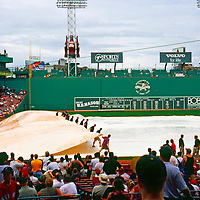 Removing the tarp at famous Fenway Park, home to the American League's Boston Red Sox. Opened April 20, 1912