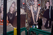 Roadworks disruption, passers-by and fashion retail models on construction hoarding in central London.