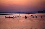 Fishing with nets thrown from boats in the wide Mekong River at sunset in Vientiane Asia