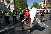 Man wearing angel wings at a demonstration in London, England, United Kingdom.