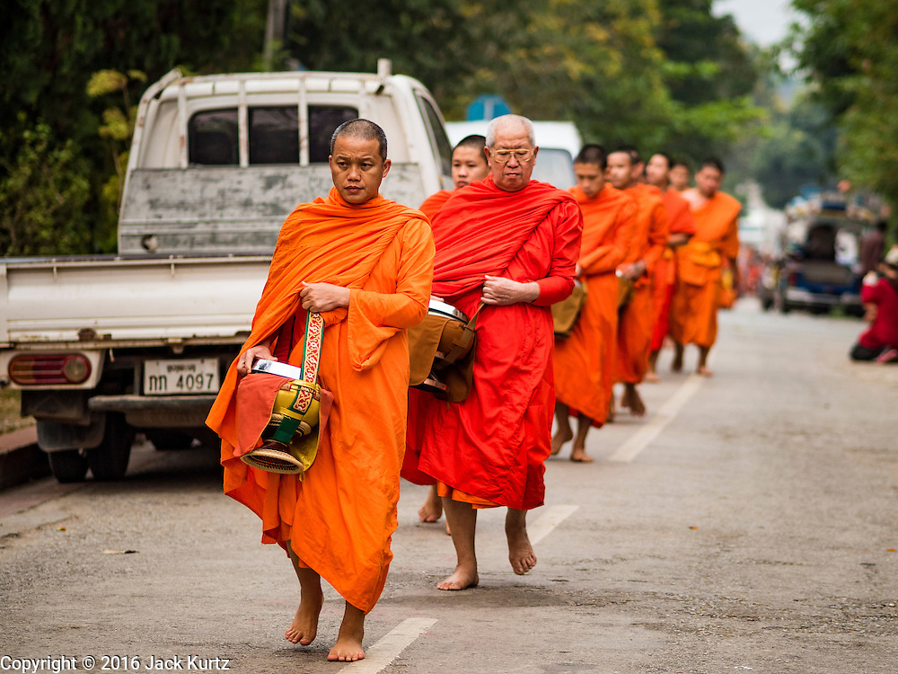 """11 MARCH 2016 - LUANG PRABANG, LAOS:   Buddhist monks walk down a street in Luang Prabang during the morning tak bat. Luang Prabang was named a UNESCO World Heritage Site in 1995. The move saved the city's colonial architecture but the explosion of mass tourism has taken a toll on the city's soul. According to one recent study, a small plot of land that sold for $8,000 three years ago now goes for $120,000. Many longtime residents are selling their homes and moving to small developments around the city. The old homes are then converted to guesthouses, restaurants and spas. The city is famous for the morning """"tak bat,"""" or monks' morning alms rounds. Every morning hundreds of Buddhist monks come out before dawn and walk in a silent procession through the city accepting alms from residents. Now, most of the people presenting alms to the monks are tourists, since so many Lao people have moved outside of the city center. About 50,000 people are thought to live in the Luang Prabang area, the city received more than 530,000 tourists in 2014.     PHOTO BY JACK KURTZ"""