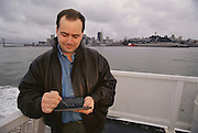 Reinhardt Quell using Cassiopeia A-10 personal computer during his ferry commute from San Francisco to Sausalito, California.  Model Released. (1997)